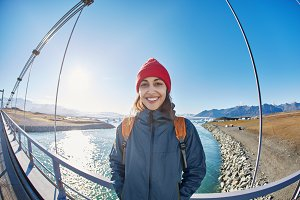 Cheerful woman walks on the brige in Jokulsarlon Ice Lagoon