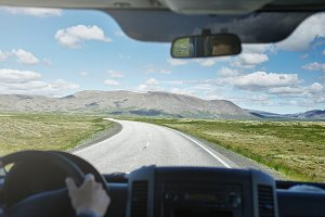 view from the car cabine on a plot of asphalt road in a bright sunny mountain landscape