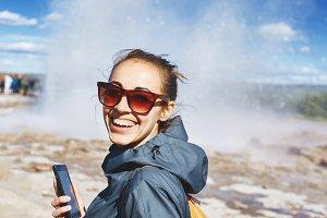 woman photographing eruption of Strokkur Geyser in Iceland