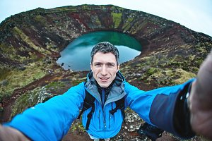 A man shoots a selfie in the background of a volcano crater.