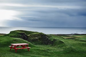 Red old homemade wooden bench on green grass
