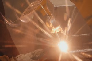 The welder welds metal parts at the plant, industrial plasma welding, modern technology