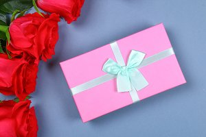 Pink roses with a gift box tied with a bow. Template for March 8, Mother's Day, Valentine's Day.