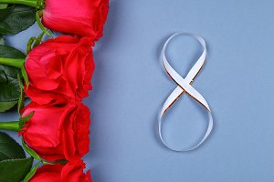 Women day image with a pink rose tied with a ribbon in shape of the number 8. Concept March 8.