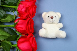 White teddy bear surrounded by pink roses on a grey table. Template for March 8, Mother's Day, Valentine's Day.