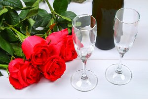 Valentines day greeting card, red rose flowers, wine glasses and gift box on wooden table. Top view.