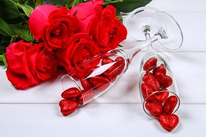 Champagne glasses filled with hearts surrounded by red roses on a white wooden table. Template for Valentine's Day.