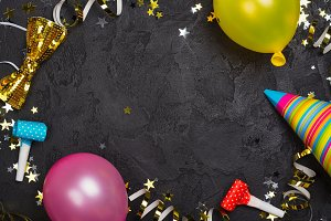 Bright festive carnival background with hats, streamers, confetti and balloons