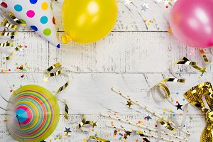 Bright festive carnival background with hats, streamers, confetti and balloons on white background