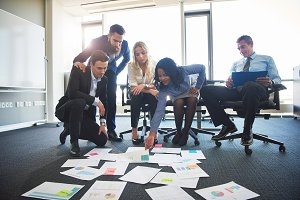 Diverse professionals discussing paperwork laid out on an office floor