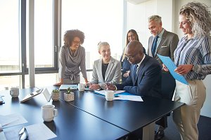 Diverse group of executives working together around a boardroom table