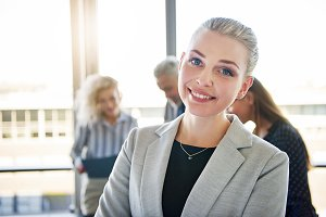 Young businesswoman smiling with colleagues talking in the background