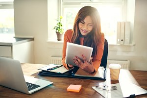 Smiling woman working with a tablet in her home office