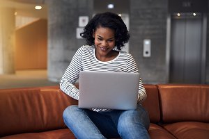 Smiling young African college student using a laptop on campus