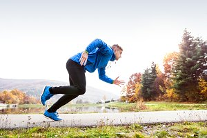 Runner at the lake on asphalt path.