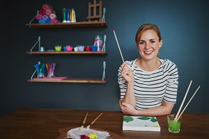 creative woman smiling at camera while painting