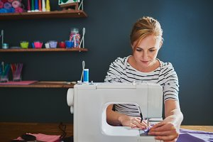 Female designer working on sewing machine