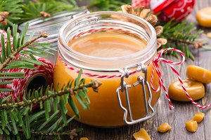Homemade salted caramel sauce in a glass jar and Christmas decor on wooden background