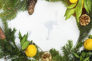 Christmas frame background with fir tree branches, pine cones and tangerines. Top view