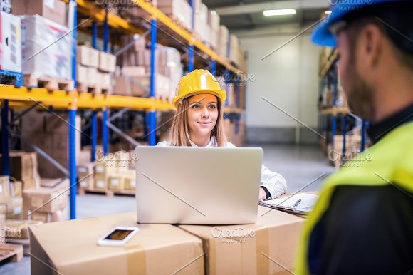 Young warehouse workers with laptop working together.