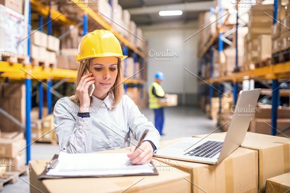 Young warehouse workers with smartphone working.