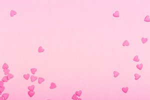 Pink heart shaped sprinkles on pink Valentines day background