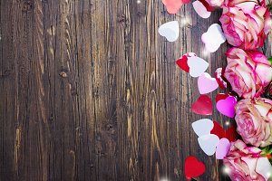 Beautiful pink rose, decorative confetti hearts on Valentines day background