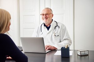 Cheerful medical worker consulting patient at laptop