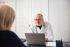 Woman in hospital talking with therapist sitting at laptop