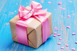 Gift box with pink bow ribbon and glitter hearts on blue spring background