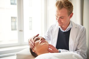 Beauty specialist holding head of lying woman in salon