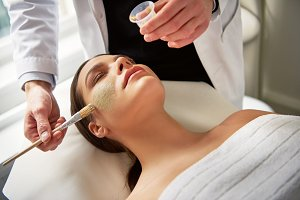 Woman lying with eyes closed while beautician putting mask