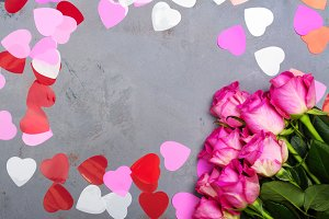 Decorative hearts and pink roses on grey stone background