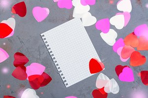 Notebook paper sheet and decorative hearts on Valentines day background