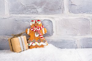 Gingerbread cookie and small gift box over white brick wall
