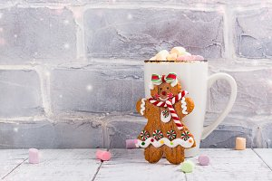 Hot chocolate with marshmallows and gingerbread girl cookie toy over white Christmas background