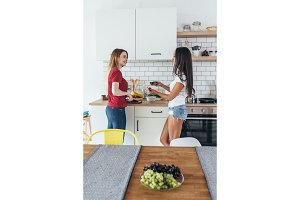 Two women in kitchen cooking talking preparing food.