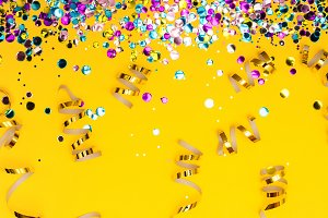 Colorful confetti and golden coiled streamers on yellow background