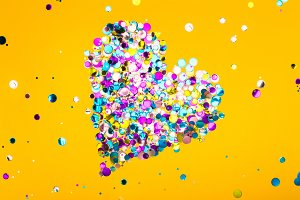 Colorful heart made of confetti on yellow background