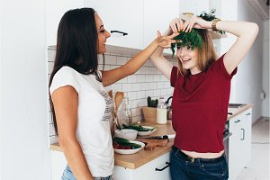 Women in the kitchen joke, laugh and have fun. Playing with vegetables