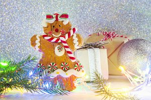 Gingerbread cookie and small gift box on bright festive Christmas background