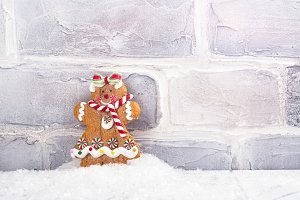 Gingerbread man cookie standing in a pile of snow near white brick wall. Christmas background