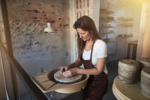 Creative artisan shaping clay on a wheel in her studio