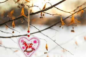 Heart shaped Valentines or Christmas decoration toy hanging on the tree branch with snow on the background