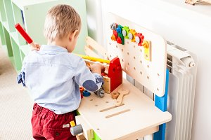 Boy plays with wooden toys