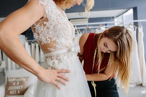 Skillful designer fitting bridal gow