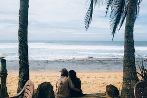 couple sitting under palm trees