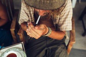The guy smokes a cigarette