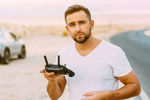 Guy controls drone with remote control