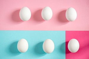 Fresh white eggs over blue and pink background